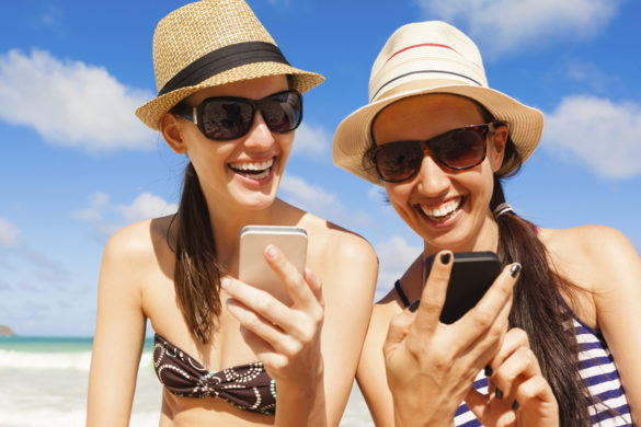 Happy beautiful women using mobile smart phone at the beach.
