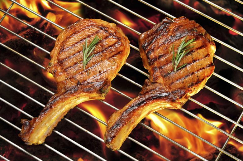 Grilled pork chops on the flaming grill