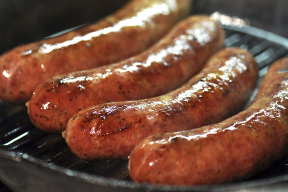 Four large sausages cooking in a cast iron skillet.