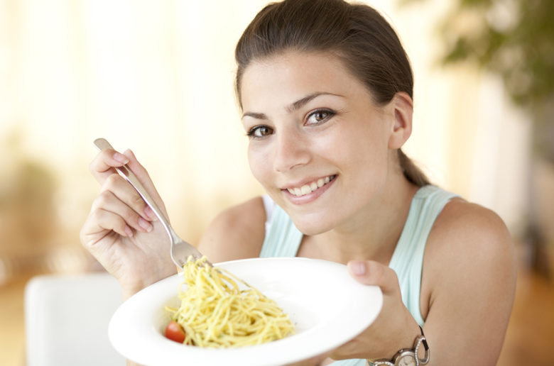Young sexy woman eating pasta in the kitchen