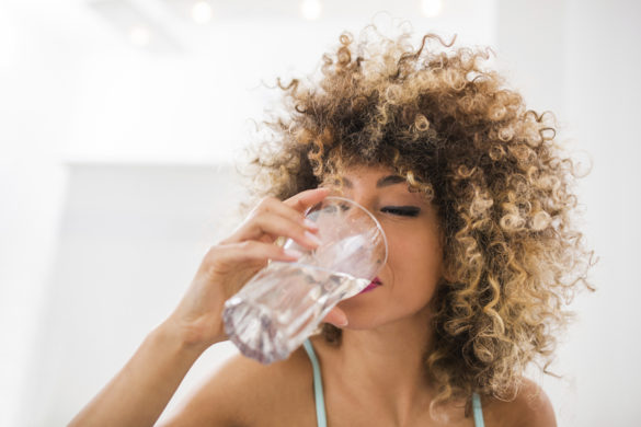 Young African American woman drinking water.