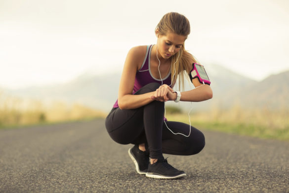 A fit female gets ready for her run listening to music along a road in Utah. She is setting her watch to help her in marathon training.