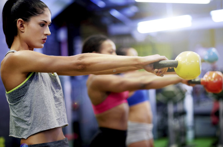 Shot of a group of women working out with kettle bells at the gym