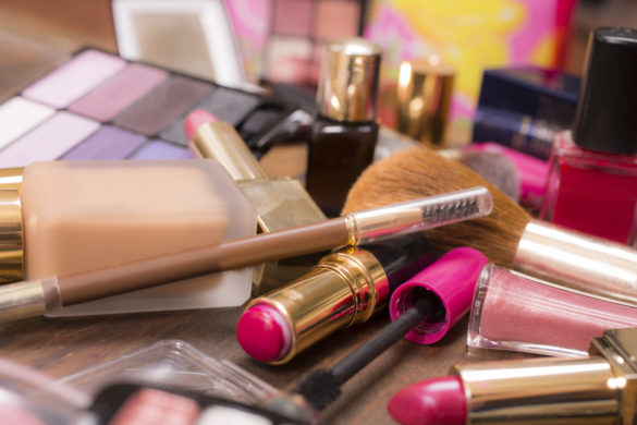 Large pile of various cosmetics lie on top of a wooden dressing table, vanity, or desk.  Make-up items include: eye shadow, nail polish, foundation, lipstick, make-up brushes,  blush, mascara, lip gloss.  Make-up artists' tools.  Great background.  Copyspace in center, top.