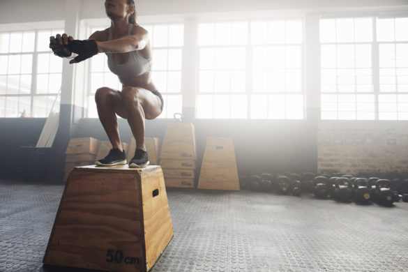 Shot of a young woman jumping onto a box as part of exercise routine. Fitness woman doing box jump workout at crossfit gym.